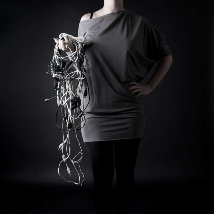 A young woman with the bunch of wires in the hand