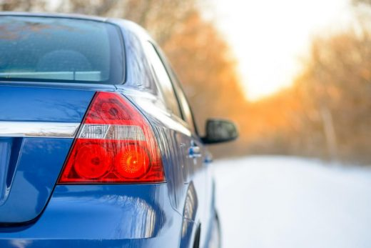 blue-car-on-the-winter-snowy-road-at-sunset-close-up-rear-view-travel-and-drive-safe-concept